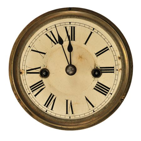 Antique clock face showing the time (three minutes to midnight), isolated on white.