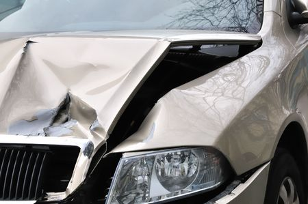 Car accident, damaged engine hood and lamp.