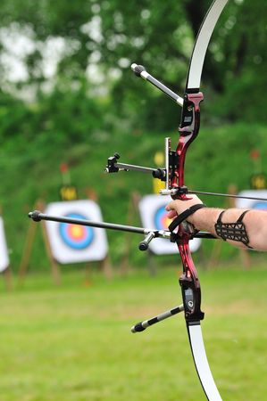 Archer pulls on the sport bow string, taking aim at his target at the competition. Stock Photo