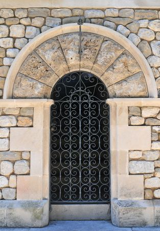 Closed metal door from outside with stone wall at old town in Besalu (Spain). Stock Photo - 7698373