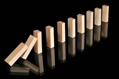 Wooden blocks with reflections representing a chain reaction isolated on black. Stock Photo