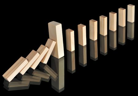 Wooden blocks with reflections isolated on black. A big massive block stops the domino effect.