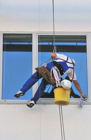 window washer: Window washers, cleaning outside on a office building.