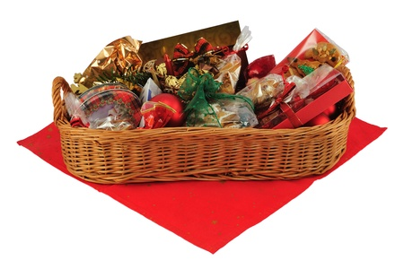 Christmas gift basket on red table cloth isolated on white.