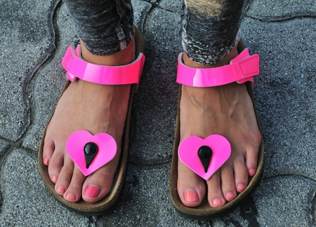 Young women feet detail with pink sandals standing on flagstone. photo