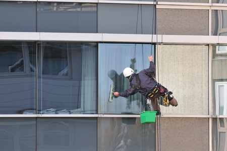Window cleaner, working on the outside of an office building. Stock Photo