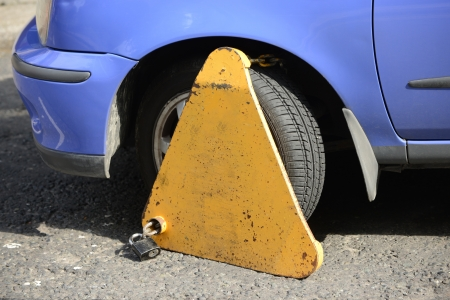 infringement: Closeup of a yellow wheel clamp attached to a blue car for a parking infringement