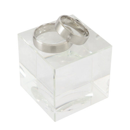cubic: A pair of white gold rings on cubic glass isolated on white