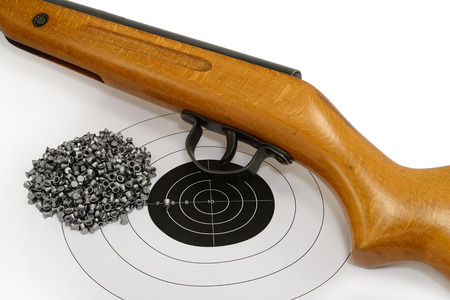 Sport shooting equipment on target. Air-gun and bullets. Stock Photo