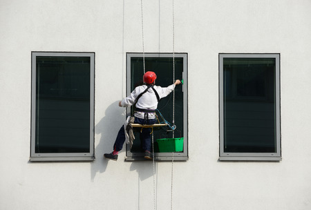 window washer: Window washer, cleaning outside on a office building.