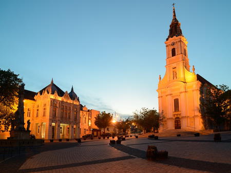 guildhall: The largest onenave church in MiddleEurope trinitymonument and Guildhall from Bela square in Szekszard Hungary at evening. Stock Photo