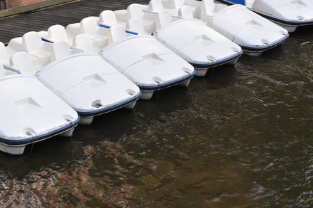 amsterdam canal: Six white paddle boats for rent in Amsterdam canal. Stock Photo