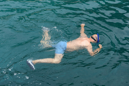 snorkelling: Man snorkelling in clear water to watch marine life. Stock Photo
