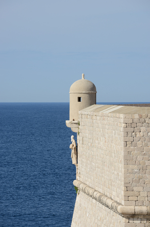 croatia dubrovnik: Stone wall and tower with St. Blaise statue overlooking sea, Croatia, Dubrovnik. Stock Photo