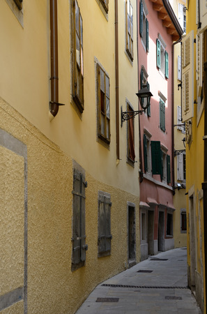 building exteriors: View of old narrow street with colored houses in Trieste, Italy.