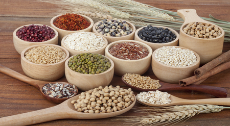 Cereal grains , seeds, beans on wooden background