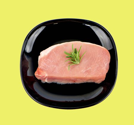 sliced raw pork meat with rosemary anisolated on yellow background