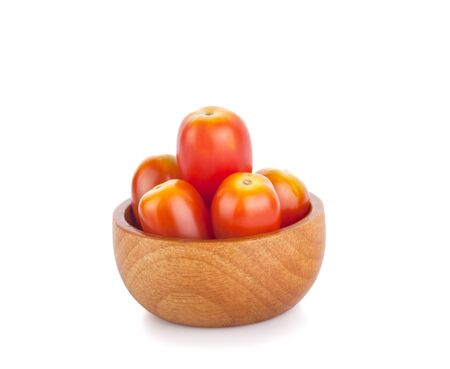 red tomatoes in wooden bowl on white background
