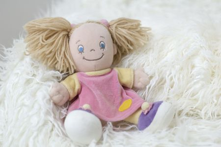 Little fabric doll lies on the white carpet Stock Photo