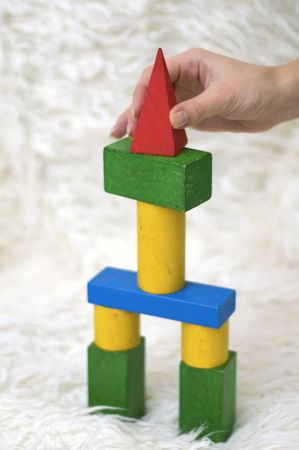 Construction of a toy tower on the white carpet