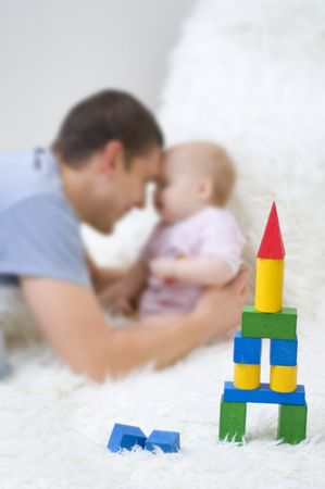 Pyramid of colorful cubes on the background of father and daughter