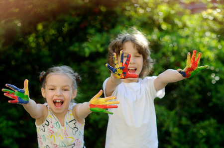 creativity: Children soiled with paint, having fun and show their dirty hands to the camera. Kids has fun and painting, drawing. Childrens creativity. Art for baby. Emotions. Children playing. Delight. Stock Photo
