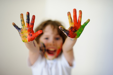 children's show: The boy himself dirty in the paint and show his dirty hands ti the camera.  Child face and hands in the paint. Child has fun by painting and drawing. Childrens creativity. Art for baby.