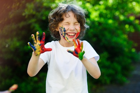Child himself dirty in the paint and show his dirty hands into the camera. Boy close his eyes and laughs, his face and hands in the paint. Childrens creativity. Art for baby. Emotions. Delight.