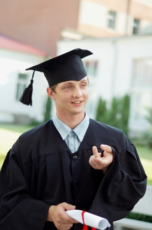 he said: The graduate of the University of something said. He is dressed in a black cloak and a hat. Student holding his diploma.