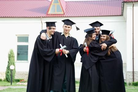 学生们手里拿着文凭。他们快乐地拥抱。年轻人穿着黑色长袍,戴着黑色帽子。