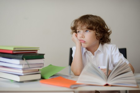 Blonde boy daydreaming. He is tired homework. On the table, books and notebooks. Imagens