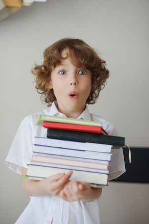expressed: Blonde boy holds a stack of books on a white background wall. His face expressed delight or surprise