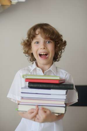 bibliophile: Curly Blonde schoolboy in white shirt holding a lot of books in his hands. On the face of the boys delight or horror. His mouth opened Stock Photo