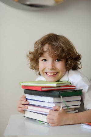 discontented: Curly boy hugged a stack of books. He rather discontented expression Stock Photo