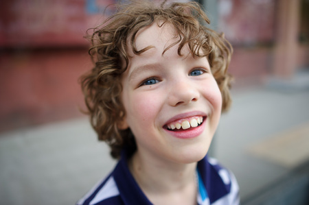 disheveled: The blue-eyed boy smiling. He has blond hair disheveled. On the face broad smile