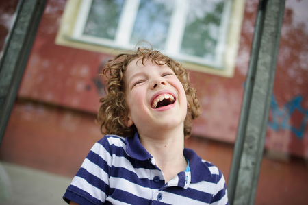 Naughty 8-9 year old boy burst out laughing. He threw his head back and closed his eyes laughing