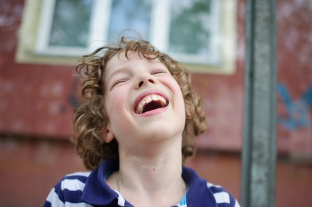 Boy laughs. He opened his mouth. It has large teeth. Head thrown back Stock Photo