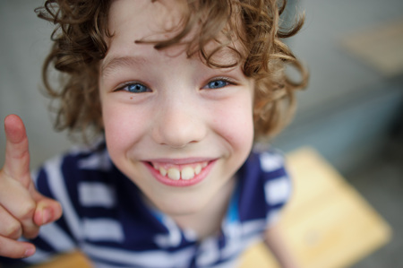 funny boy: Funny boy smiling. He has blue eyes, big teeth and a snub nose. Boy shows something finger Stock Photo