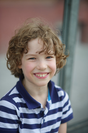 sincerely: Curly boy smiling sincerely. He is dressed in blue-and-white T-shirt. The boy has blue eyes and big white teeth.