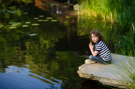 The boy sits on a rock on a background of a picturesque lake. Stock Photo