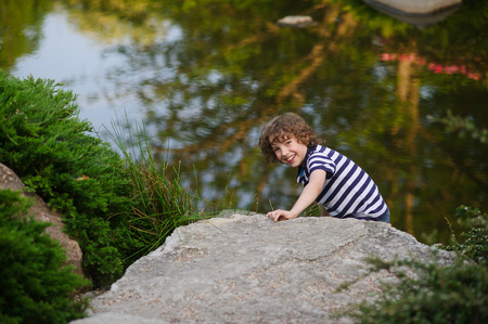 Blonde boy hiding behind a boulder near the pond. Behind him, expanse of water.
