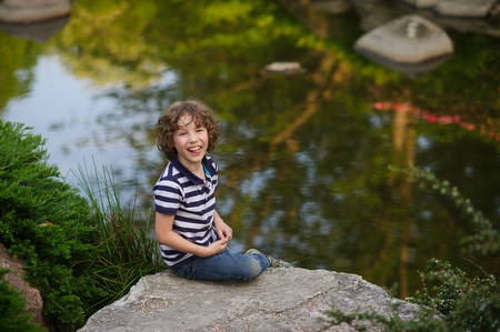 8-9 years boy sitting on a big stone near the pond. The child laughs. He stuck out his tongue Stock Photo