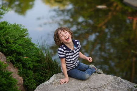 8-9 years boy sitting on the boulder resting at the pond. The child is having fun. He laughs loudly Behind the picturesque pond
