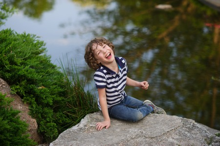 Blonde boy 8-9 years old sitting on a large rock in a pond. He laughs merrily. Behind the boys beautiful pond