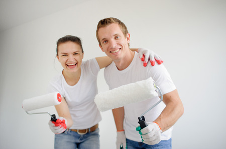 Boy and girl on the background of a white wall. In the hands of rollers for painting. Both are smiling