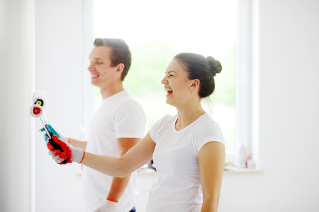 refurbish: Girl and a guy in a white T-shirts painted wall. They hold the rollers. On gloves hands