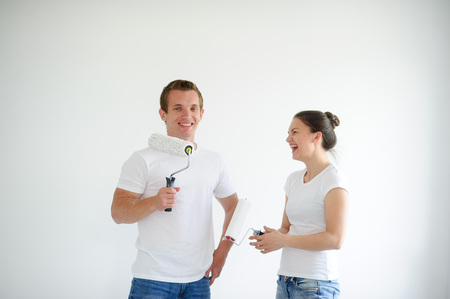 Boy and girl holding hands in the rollers. They rejoice in the end of the repair. Behind them, a white wall