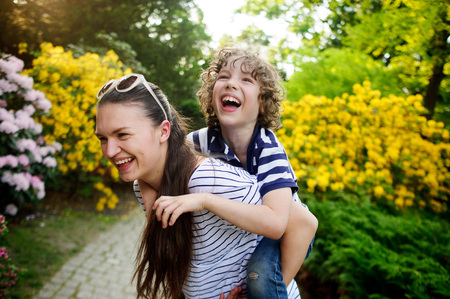 good boy: The girl with dark long hair carries on his shoulders the mischievous brother. They have a good mood. Around the a flowering garden