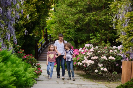 best way: Young mother prvela son and daughter in a Japanese garden. Children 7-8 years of age. They thrive in nature. Children enthusiastically tell something mom. The best way to relax with the kids on the weekend