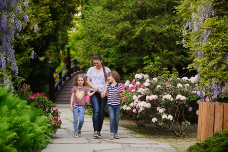 best way: Young mother walking with her daughter and son. They are surrounded by picturesque greenery. Family discussing something. Walking in nature the best way to strengthen child health Stock Photo